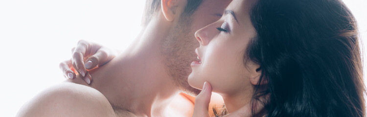 panoramic shot of young man passionately kissing brunette woman with closed eyes isolated on white