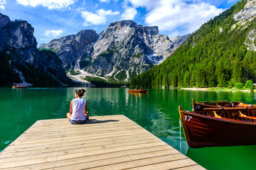 Woman relaxing on Pier at Lake Braies also known as Pragser Wildsee  in beautiful mountain scenery. Amazing Travel destination Lago di Braies in Dolomites, South Tyrol, Italy, Europe. Wall mural