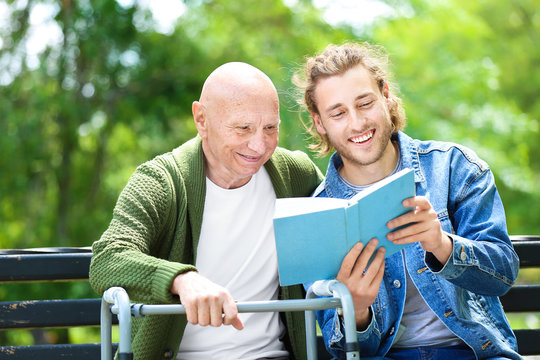 Young man reading book to his elderly father in park