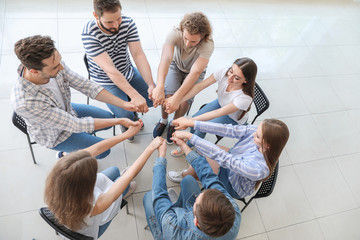 Fotomurales - Young people holding hands together at group therapy session