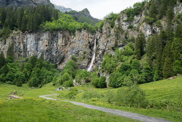Fotomurales - landscape view of a high picturesque waterfall in lush green forest and mountain landscape