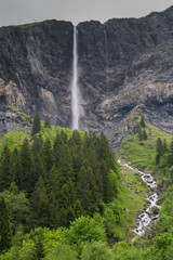 Wall Mural - high waterfall plummets off a rock and grass cliff in the Swiss Alps