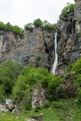 Wall Mural - vertical view of a high picturesque waterfall in lush green forest and mountain landscape