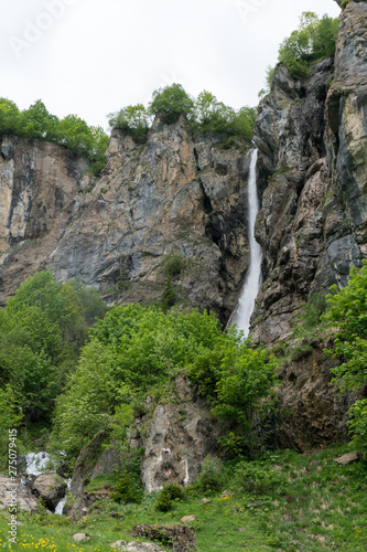 Wall mural vertical view of a high picturesque waterfall in lush green forest and mountain landscape