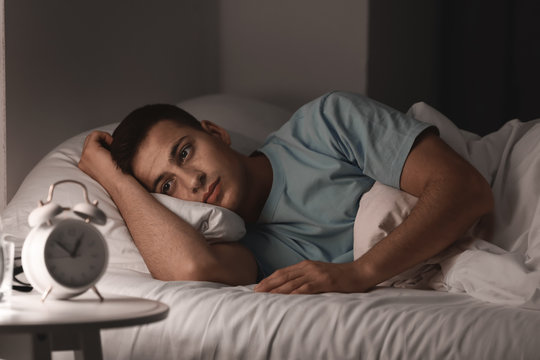 Young man suffering from insomnia while lying in bed at night