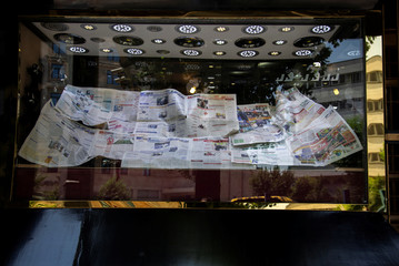 Newspapers cover display at a gold shop in Tehran