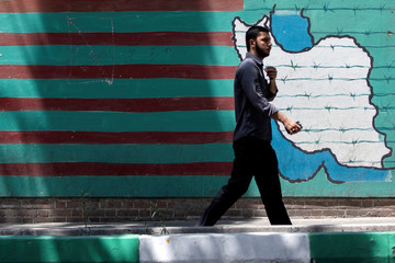 A man walks past the mural showing U.S. flag with barbed wire in Tehran