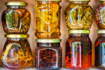 Jars with honey and natural colorful herbs for sale on shelves