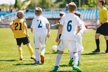 A mixed-gender soccer team playing a football match. Junior soccer tournament game