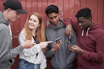 Group Of Teenage Friends Looking At Mobile Phones In Urban Setting