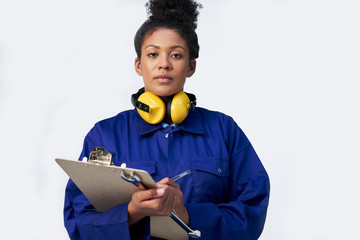 Portrait Of Studio Shot Of Female Engineer With Clipboard And Spanner Against White Background