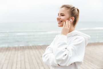 Image of happy nice woman smiling and listening to music with earpods while walking near seaside
