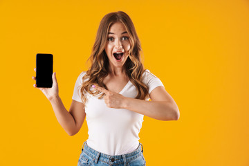Image closeup of pretty caucasian woman wearing basic t-shirt rejoicing while pointing finger at cellphone
