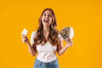 Photo of ecstatic delighted woman rejoicing while holding fan of dollar money and credit card