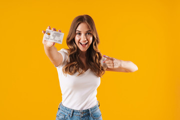Photo of caucasian young woman rejoicing while holding and pointing finger at credit card