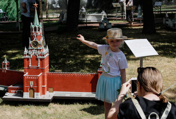 """People take pictures near a model of the Kremlin's Spasskaya Tower is seen at the """"RussiainMiniature"""" exhibition in Moscow"""