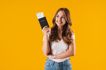 Photo of positive young woman smiling while holding passport and travel tickets