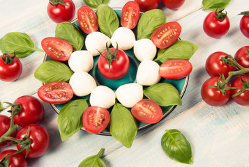 Tomato and mozzarella with basil leaves on a plate. Caprese salad.