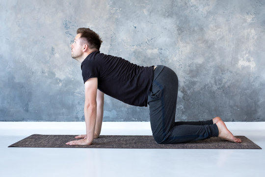 Young yogi men practices yoga asana bitilasana or cat cow pose