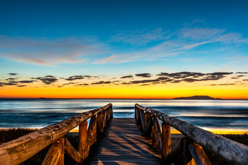 beautiful landscape with wooden walkway to seascape beach at sunrise with blue and orange sky and island in the background
