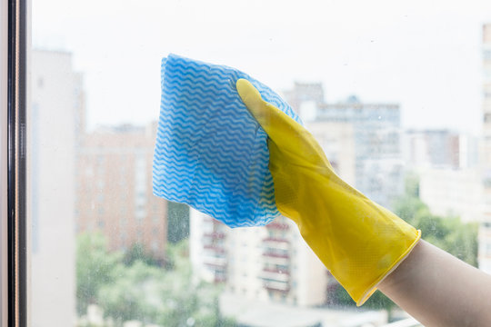 hand wipes glass of home window by blue rag