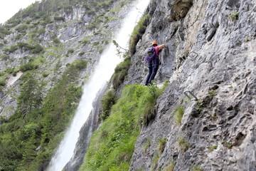 Klettersteig führt duch die Felswand an Wasserfall