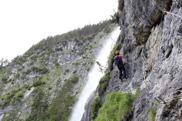 Frau klettert neben Wasserfall