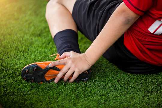 footballer is sitting and catch the ankle of the feet because of pain, soccer player was injured in the foot.
