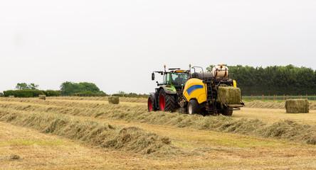 Tractor on farm bailing straw