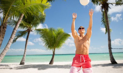 summer holidays, sport, fitness and people concept - young man with ball playing volleyball over tropical beach background in french polynesia