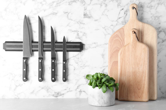 Magnetic holder with set of knives on marble wall in kitchen