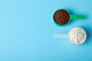 Scoops of different protein powders on light blue background, flat lay with space for text