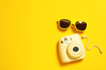 Sunglasses and camera on color background, top view with space for text. Beach accessories