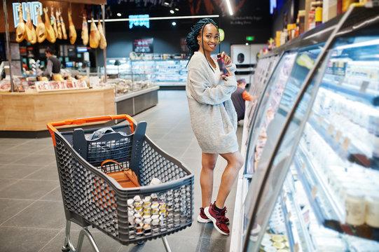 African woman with shopping cart choose yogurt bottle from fridge at supermarket.