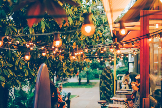 Friendly youth atmosphere in a cozy outdoor summer terrace in a coffee shop. Street garland decorates the space. Defocused image to convey the mood, blurred background.