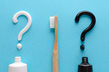 question from white and black toothpaste, teeth care concept, wooden toothbrush on blue background