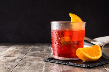 Negroni cocktail with piece of orange in glass on wooden table. Copysace