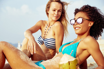 Two smiling young female friends suntanning together on a beach