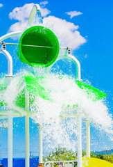 Detail of the children's water playground attraction, waterpark - the green bucket of water at the moment of pouring.