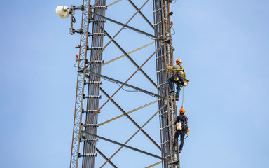 Telecom maintenance. Two repair men climbing on tower against blue sky background Fotomurales