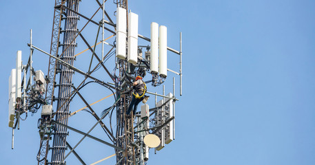 Telecom maintenance. Man climber on tower against blue sky background Fotomurales