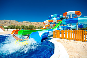 colorful open-air water slides with a child coming into the pool, view at an angle