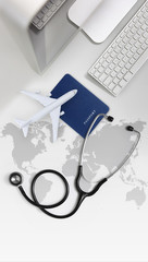 international medical travel insurance concept, stethoscope, passport, computer and airplane on desk office with global map