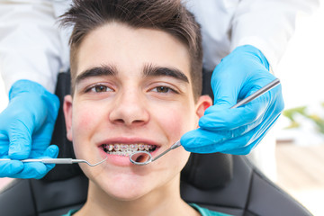 dentist with tools in the young man's mouth with orthodontics