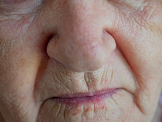Elderly woman 70 years. Face close up. Eyes, eyebrows, lips, nose. Shallow focus. Village warlock, quack