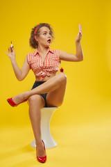 Model sitting, applying red polish, looking at nails.