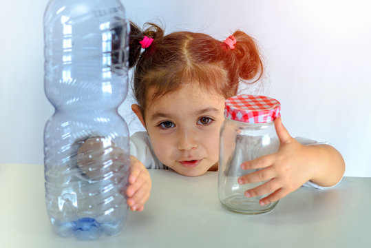 Save the world plastic free. Conceptual image for anti plastic campaign.Child pushing the plastic bottle, holding glass jar. No to Plastic Containers, Yes to Glass Jars.
