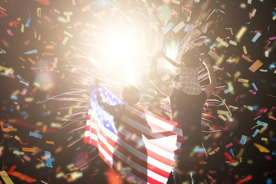 Great holiday of a great country. The celebration of Independence Day in the United States of America. The happy family looks holiday fireworks in the evening sky