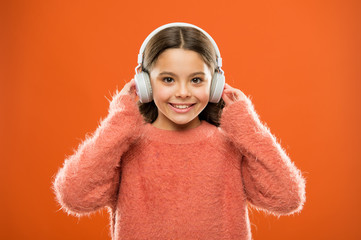 Perfect sound stereo headphones. Girl cute little child wear headphones listen music. Kid listen...