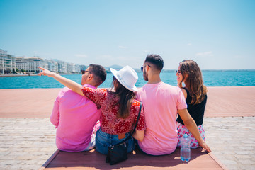 Four tourist friends having fun and taking pictures on a modern abstract bench paced on a seaside marine port on a sunny day. Enjoying the beautiful blue and turquoise sea.